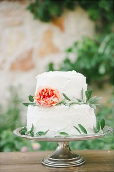 simple two tiered cake with flowers and some eucalyptus; like the rough, natural icing