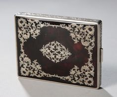 "A large and outstanding tortoiseshell and silver applique cigarette case. Heavy silver central band profusely engraved.  4""h x 3""w x 1/2""d. ~   circa 1890"