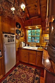 Rustic Kitchen with Wood paneled wall, Wood paneled ceiling, Task lighting over kitchen sink, Wood countertops