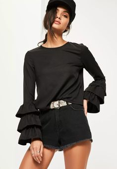 Play up your feminine side in this black blouse with ruffled sleeve detailing and a back split.
