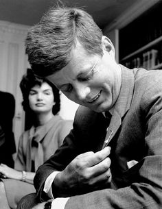 Jacqueline and John Kennedy, who is admiring his pin in the shape of a broom, illustrating hope of democrats making a clean sweep in the 1958 elections.