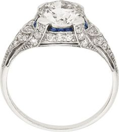 Art Deco Diamond, Sapphire, Platinum Ring, J. E. Caldwell  The ring features a European-cut diamond measuring 7.25 x 7.23 x 4.27 mm and weighing approximately 1.30 carats, enhanced by French-cut sapphires weighing a total of approximately 0.10 carat, accented by European-cut diamonds weighing a total of approximately 0.50 carat, set in platinum, having a partial J. E. Caldwell signature