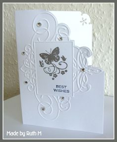 Flower Sparkle - dry emboss the frame onto the card front, stamp the butterfly image with VersaMark ink and heat embossed it with detail silver embossing powder, navy ink for the sentiment, cut round part of the dry embossed design on the card front so card is shaped, punched the back inside of the card with a decorative corner punch, and added bling