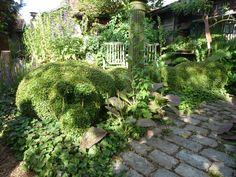 Een paadje van herbruikte oude kasseien leidt naar het tuinhuisje.