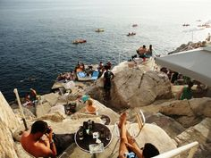 """Buža I and Buža II  Ispod Mira 14, Crijevićeva 9  Visitors must pass through a hole (or """"buža"""" in Croatian) in the fortress walls to access these seaside bars. The reward is one of the most stunning views in all of Dubrovnik. From Buža I, you can easily climb a ladder down to the sea below. Buža II is a little more polished and draws an older crowd."""