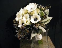 This all-white winter wedding bouquet was created with Dusty Miller greens, Viburnum berries, and white Anemones