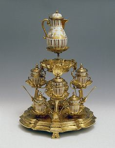 Chocolate Set on a Stand  Irminger, J.J. (model); Seuter, Abraham (painting).  Germany, Meissen. Circa 1715-1730 Porcelain and silver; cast, chased, engraved, gilding and painted in gold. H. 20.3 cm (coffee-pot), h. 40.2 cm (stand)  The State Hermitage Museum
