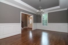 White wainscoting walls in the formal dining room, with SW 7018 Dove Tail Grey paint above the trim and in the trey ceiling.
