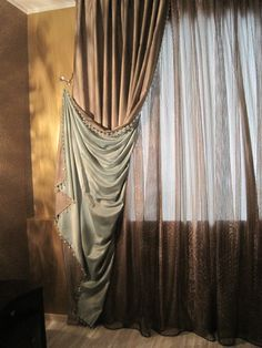 A dramatic pulled back drape contrast lined and complimented with a copper sheer. delightful!