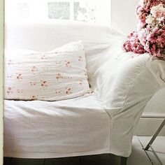 I could stay on this couch all day and read! Love that pale flowered pillow and I can just smell those fresh flowers