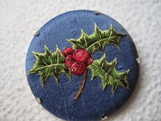 Margaret Dier Embroidery. hand embroidered holly brooch. Silk shaded long and short thread painting on a silk dupion background. 2 inch diameter.