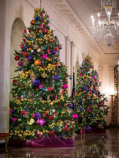 On either side of the door leading to the Blue Room are two holiday trees strung with garlands of jewel-toned ball ornaments.