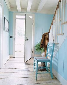 Blue hallway :: I luv how much the simple blue chair adds to the look.