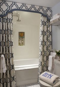 I love this look! Shower curtains on both sides to create a luxurious look (and hides all the shampoo and things) and the runner on the top to hide the bar. GORGEOUS.