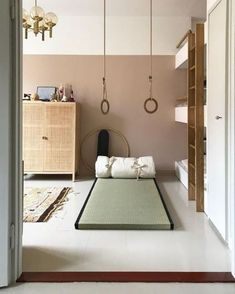 Minimalist kids room with mattress on floor, hanging rings for play, and three quarter painted wall for style room decor
