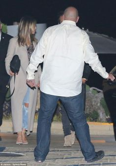 Romantic evening: Jennifer Aniston wore distressed blue jeans, patterned blouse and long cream-colored coat for a dinner date in Malibu with hubby Justin Theroux on Sunday night