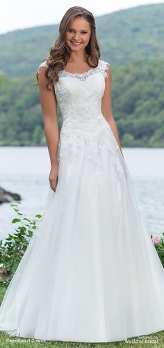 A 1950's inspired corded lace ball gown with a scoop neckline, dropped waistline, sheer V-back, and chapel length train.
