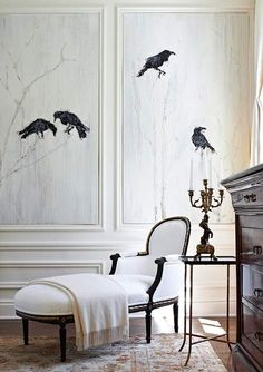 This view of the 2011 Lake Forest Showhouse master bedroom reveals one of the tranquil room's few decorative indulgences, stone-etched panels depicting a smattering of ravens. The black birds relate to the room's black-frame chaise and bed, providing just enough contrast for interest without ruffling the heavenly white calm. Designed by Gail Plechaty.