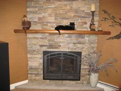 Wooden Fireplace Mantels Decorating With Candle And Black Cat ~ http://lanewstalk.com/decorating-fireplace-mantels-in-modern-art-way/