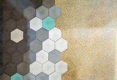 G-Roc apartment, Barcellona: dettaglio sui materiali utilizzati. Piastrelle e mattonelle esagonali separano a metà il pavimento della cucina