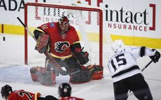 Los Angeles Kings left wing Andy Andreoff (15) has his shot deflected by Calgary Flames goaltender Mike Smith (41) during the first period of an NHL hockey game Wednesday, Jan. 24, 2018, in Calgary, Alberta. (Jeff McIntosh/The Canadian Press via AP)