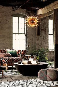 Living room: Grey brick walls, red printed couch, yellow spiked light fitting, circular black table