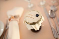 pale pink satin linens, homemade button napkin rings and homemade spiced blackberry jam favor