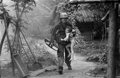 A U.S. infantryman from A Company, 1st Battalion, 16th Infantry  carries a crying child from Cam Xe village after dropping a phosphorous grenade into a bunker cleared of civilians during an operation near the Michelin rubber plantation northwest of Saigon, August 22, 1966. A platoon of the 1st Infantry Division raided the village, looking for snipers that had inflicted casualties on the platoon. GIs rushed about 40 civilians out of the village before artillery bombardment ensued. (AP…