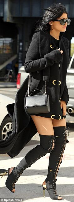 Showing some skin: Kylie teamed her kinky over-the-knee boots with a black mini-dress featuring gold detail