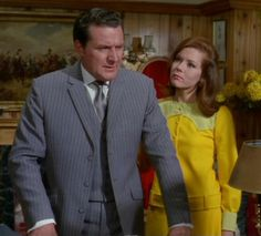 'You Have Just Been Murdered', Series 5 ~ Steed's ever present grey pinstripe suit. Worn in 7 episodes! Here he pairs it with a white shirt and metallic grey silk tie. Emma is wearing a sunflower yellow, collarless, shirt-style mini dress with pale yellow yoke and cuffs. Drop waist with belt accent.