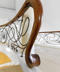 ST490 Dwustronne policzkowe schody gięte montowane na wylewce betonowej. Policzki z malowanego dębu, balustrada z ręcznie kutej stali z drewnianym pochwytem. Stopnice kamienne. Realizacja w prywatnej rezydencji, Projekt – TRĄBCZYŃSKI.