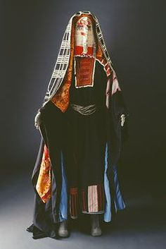 The region in which al-Madinah sits was dominated by the great bedouin tribe of Harb. They conducted the caravan trade between central Najd, al-Madinah, Makkah and Jeddah.    Typical Harbi dresses are decorated with buttons and embroidery, with heavy patchwork on the hem. Blue cotton cloth was a particular Harbi trademark. Coins were often used as jewelry, as on this burqu'.