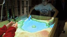 Augmented Reality Sandbox.'   This was a project created by UC Davis Department of Technology in conjunction with Microsoft Kinect. Users were able to manipulate the sand to alter the real-time interactive augmented map. The aim was to physically create topographic models and snapshot the creations with a computer for future science museums.