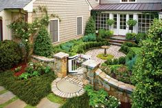 The cottage garden courtyard ties the orginal home to the addition and has an intimate scale. Partially hidden from the street below, it creates intrigue—only the stone wall, gate, and a few plants can be seen. As you approach the front door, the 22½- by 27-foot space comes into view as a garden within the larger landscape. See More of the Cottage Garden