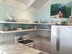 HomeGoods accessories spice up functional open shelving in this tiny but efficient beach cottage kitchen. Sponsored by HomeGoods Happy By Design