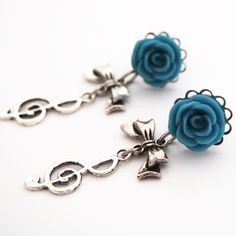 Cool blue roses on a stainless steel plug, with a metallic bow and metal treble clef dangling below them. Available at glamsquared :)