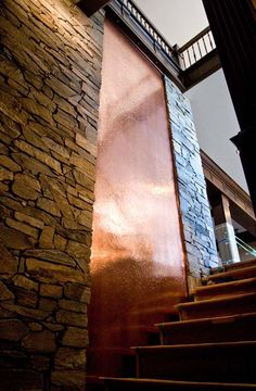 Copper Water Wall (atrium) along side steps. love the copper metal color and reflection of the light and the subtle water effect coming down the wall. creates a great interior design water feature for public entry spaces Glass Waterfall, Indoor Waterfall, Pool Waterfall, Copper House, Copper Wall, Copper Metal, Wall Of Water, Water Walls, Stairs In Kitchen