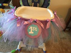 High chair tutus  Items needed: Ribbon Tulle Stock paper in assorted colors Scissors Glue Piece of cardboard (to measure the tulle.)  Elastic band Hot glue gun  Directions:  Make bows and set aside. Make 1st sign and let dry. Cut the cardboard into desired length. Use cardboard and wrap the tulle around and cut. Take the elastic band and put the tulle around it (as if you're making a tutu.) Then hot glue bows and 1st sign on.