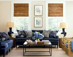Living room with two navy sofas with white piping and blue and white floral and chevron printed accent pillows,two wicker armchairs with blue cushions, a wood coffe table with metal legs, matching wicker side tables with black lamps and encasement windows
