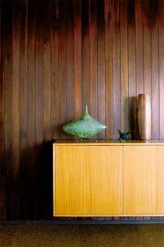 "Dark word paneled walls an light wood lowboy in the Googie/Populuxe style.     (Via Homelife Australia with photographer Richard Powers— ""Iconic Malibu Beach Home."")"