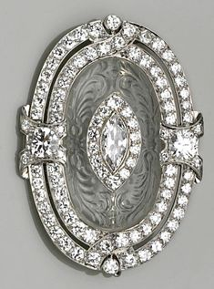 An art deco rock crystal, diamond and platinum brooch, circa 1920 centering a marquise and old European-cut diamond cluster within a carved rock crystal oval panel and further two-row old European-cut diamond frame; estimated total diamond weight: 6.50 carats.