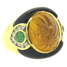 An 18k yellow gold cocktail ring adorned with a carved citrine, onyx, emeralds and diamonds  DESIGNER: Not Signed  MATERIAL: 18K Gold  GEMSTONE: Diamond, Emerald, Citrine, Onyx  RING: STYLE Ring  DIMENSIONS: The ring is a size 5 and the top of the ring is 18mm x 20mm  WEIGHT: 14.9g  CONDITION: Estate  PRODUCT ID: 15707