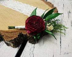 Dark burgundy groom's boutonniere preserved greenery sola