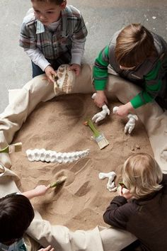 """paleontologists pit"" - paint brushes in the sand table to sweep sand off dinosaur fossils."