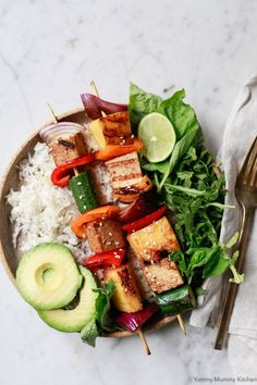 Grilled vegetable, pineapple, and tofu shish kabobs served with rice, salad, and avocado. This grilled veggie kabob recipe is so easy and perfect for a vegetarian or vegan BBQ. #vegan #veganrecipes #veganfood #bbq #grill #recipe #pineapple #tofu #vegetarian #vegetarianrecipes