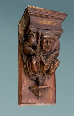 Decorative corbel of a Medieval man reading a book. It was probably designed to be hung high in a library. It is made out of plaster with a faux wood finish mounted on a wooden backboard. The Gothic revival style was very popular during the early 20th century, and similar whimsical reading figures carved from stone can be found decorating building exteriors all around New York City. We'll take $400 off the list price through July 15, 2016.