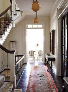The airy second-floor landing, with its antique alabaster pendants and a gorgeous distressed runner, captures Darryl's love of timeworn treasures that are none too precious.