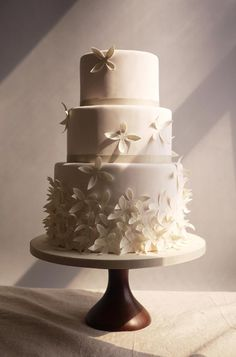 A bevy of white blooms add a simple but whimsical touch to this three-tiered wedding cake.