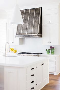 Bright all-white kitchen with a stainless steel stove, subway tile backsplash, a kitchen island, and a white pendant light