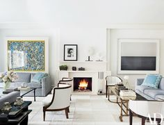 The living room of Nina Bauer and Andrew Shapiro's New York City apartment, which was renovated by architect David Ruff of Design Laboratories and decorated by Penny Drue Baird of Dessins. The space serves as a gallery for works by, from left, Damien Hirst, William Klein, and Hiroshi Sugimoto. The angular armchairs are 1930s French, the barrel-back bergères are from Lee Calicchio, and the cowhide rug is by Stark Carpet | archdigest.com